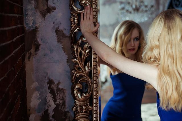 Blondynka w niebieskiej sukience przed lustrem