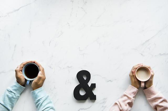 Kubek z czarną i białą kawą trzymane w dłoniach