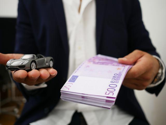 Mężczyzna trzyma plik banknotów i model samochodu
