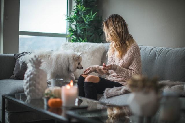 Kobieta siedząca na sofie z psem